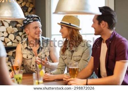 people, leisure, friendship and communication concept - group of happy smiling friends drinking beer and cocktails at bar or pub - stock photo