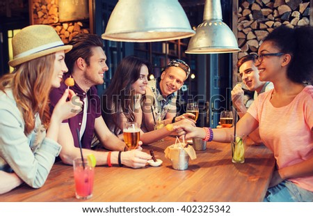 people, leisure, friendship and communication concept - group of happy smiling friends drinking beer and cocktails eating and talking at bar or pub