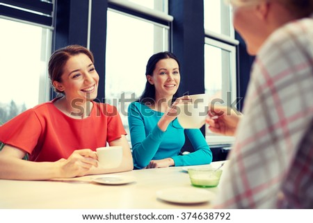 people, leisure, friendship and communication concept - happy young women meeting and drinking tea or coffee at cafe - stock photo