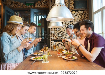 people, leisure, friendship, technology and internet addiction concept - group of happy smiling friends with smartphones taking picture of food at bar or pub - stock photo