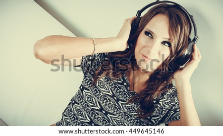 People leisure relax concept. Young woman in big headphones listening music mp3 relaxing toned image - stock photo