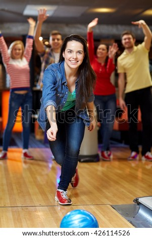 people, leisure, sport and entertainment concept - happy young woman throwing ball in bowling club - stock photo