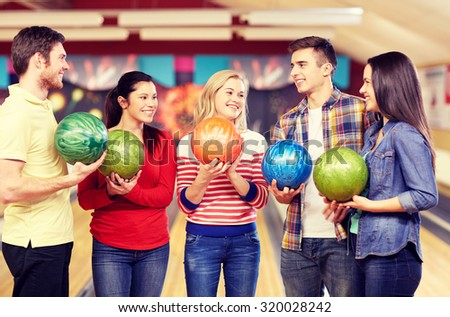 people, leisure, sport, friendship and entertainment concept - happy friends holding balls and talking in bowling club - stock photo