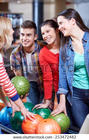 people, leisure, sport, friendship and entertainment concept - happy friends in bowling club - stock photo