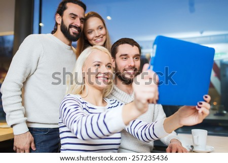people, leisure, technology and friendship concept - happy friends with tablet pc computer taking selfie at cafe - stock photo