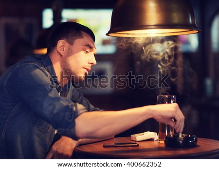 people, lifestyle and bad habits concept - man drinking beer and smoking and extinguishing his cigarette at bar or pub - stock photo