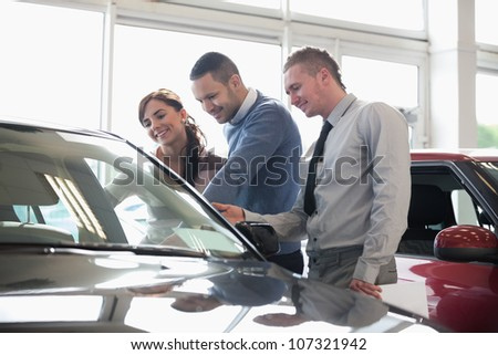 People looking at a car in a car shop