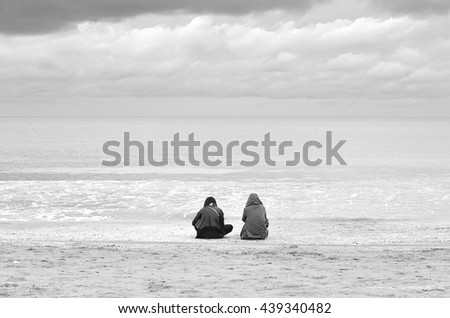 people looking the sea with cloudy sky in winter - stock photo
