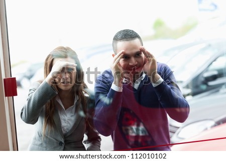 People looking through a shopwindow of a dealership - stock photo
