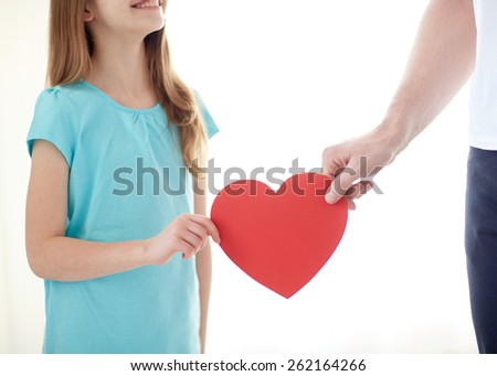 people, love, charity and family concept - close up of girl and male hand holding red heart shape at home - stock photo