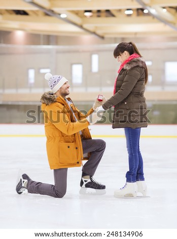 people, love, proposal, sport and leisure concept - happy couple with engagement ring on skating rink - stock photo