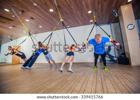 People make fitnes exercise with a band in the gym. - stock photo