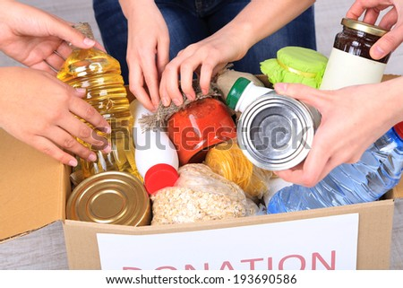 People makes foodstuffs out of donation box on grey background - stock photo