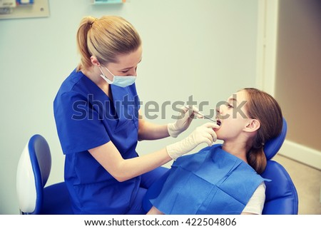 people, medicine, stomatology and health care concept - happy female dentist with mirror checking patient girl teeth up at dental clinic office
