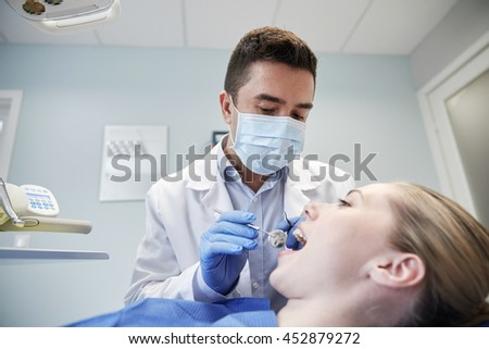 people, medicine, stomatology and health care concept - male dentist in mask with dental mirror and probe checking female patient teeth up at dental clinic office - stock photo