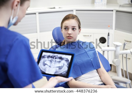 people, medicine, stomatology, technology and health care concept - female dentist showing teeth x-ray on tablet pc computer to patient girl at dental clinic office