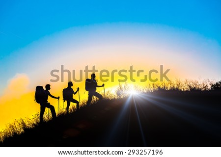 People meeting sunrise team building session. Group of people silhouettes walking toward mountain summit with backpacks and hiking trekking gear meeting uprising sun sunbeams and blue sky background - stock photo