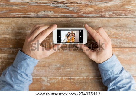 people, memory, relations and technology concept - close up of male hands holding smartphone with photo of happy friends on screen at table - stock photo
