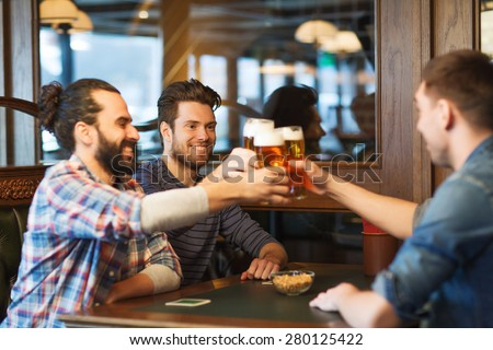 people, men, leisure, friendship and celebration concept - happy male friends drinking beer and clinking glasses at bar or pub - stock photo