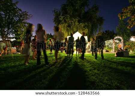 people mingling at a free concert by local musicians - stock photo