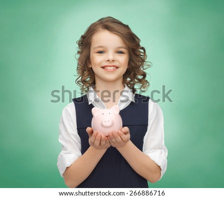 people, money, finances and savings concept - happy girl holding piggy bank on palms over green chalk board background - stock photo
