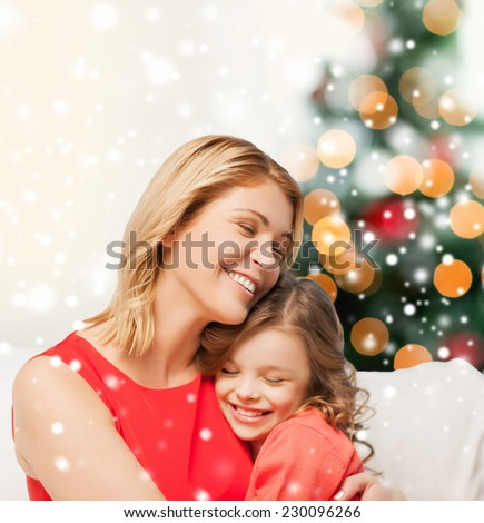 people, motherhood, family, christmas and adoption concept - happy mother and daughter hugging at home - stock photo