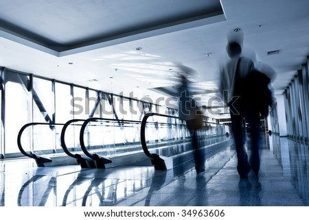 People move in glass corridor in airport