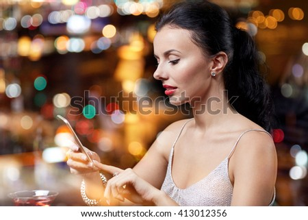 people, nightlife, technology and holidays concept - young woman texting on smartphone at night club or bar