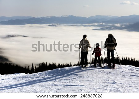 People observing mountain scenery. Family of three people stays in front of scenic landscape. These are skiers, they dressed in winter sport jackets and have skies attached - stock photo
