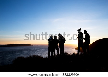 people on bank of sea with sunrise sky