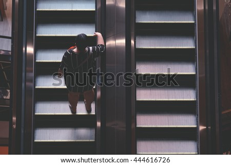 People on escalator, over view - stock photo