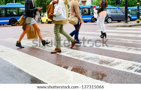 People on rain wet zebra crossing - stock photo
