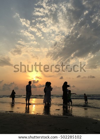 People on sea beach at sunset having fun