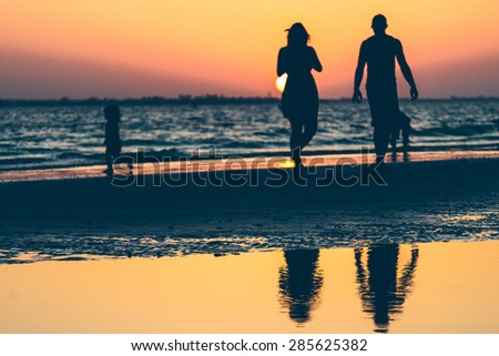 People on the Beach at Sunset - stock photo