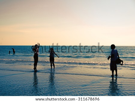 People on the beach  silhouette in summer with enjoy activity relaxing and taking photograph instagram-like tone vintage