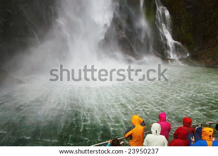 People on the boat near spectacular waterfall, Milford Sound fiord, New Zealand - stock photo