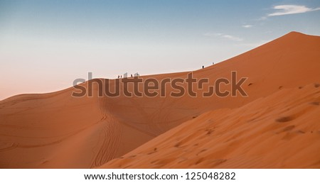 People over dune at sunset in the desert of Morocco