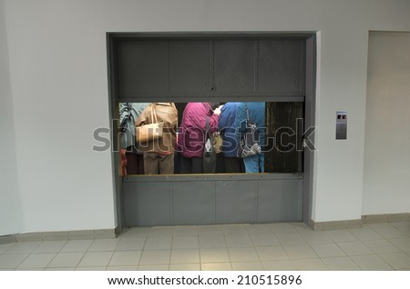 people packed into freight elevator - stock photo