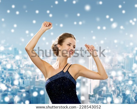 people, party, holidays and christmas concept - smiling woman dancing with raised hands over snowy city background - stock photo