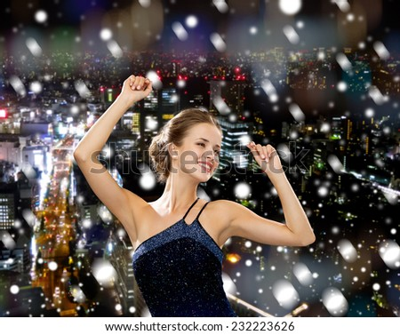 people, party, holidays and christmas concept - smiling woman dancing with raised hands over snowy night city background - stock photo