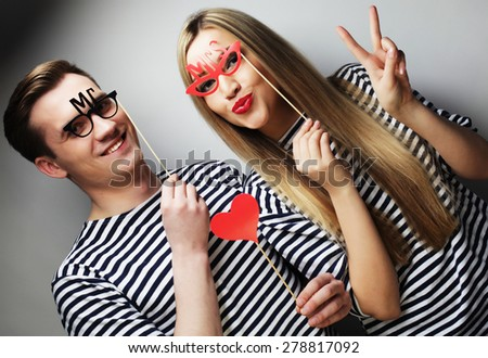 people, party, love and leisure concept - lovely couple holding party glasses and hat on sticks, over gray background - stock photo