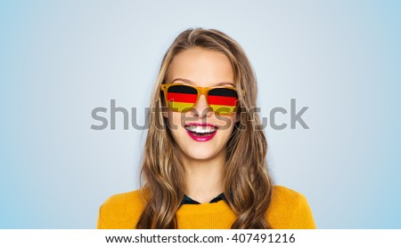people, patriotism and nationality  concept - happy young woman or teen girl face in sunglasses with german flags over blue background - stock photo