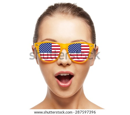 people, patriotism, national pride and independence day concept - happy teenage girl in shades with american flag - stock photo