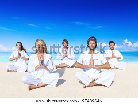 People performing yoga on the beach. - stock photo