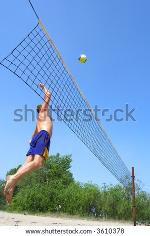 People playing beach volleyball - fat man jumps high to strike the ball. Shot near Dnieper river, Ukraine.