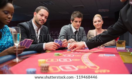 People playing poker at the table in casino - stock photo