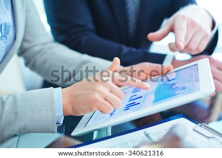 People pointing at graphs in touchpad at meeting