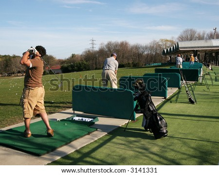people practicing at driving range - stock photo