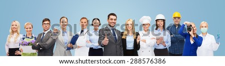 people, profession, qualification, employment and success concept - happy businessman over professional workers showing thumbs up over blue background - stock photo