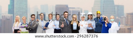 people, profession, qualification, employment and success concept - happy businessman over professional workers showing thumbs up over city background